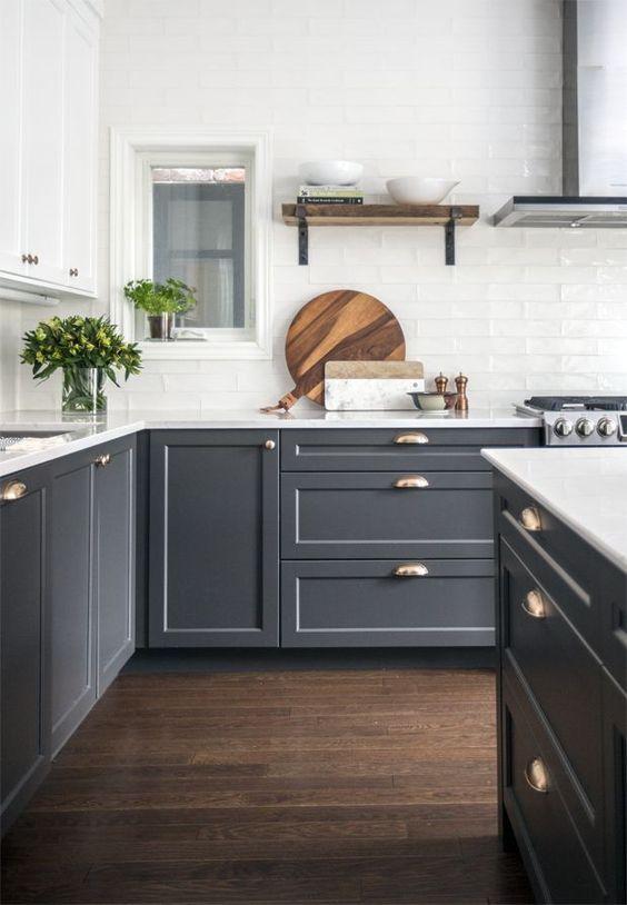 una cucina bicolore con armadi bianchi e grigi, un paraschizzi in piastrelle bianche e tocchi in ottone è molto elegante