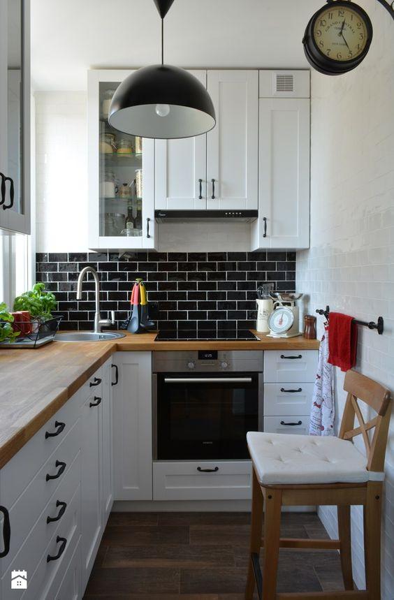 una piccola cucina ad angolo bianca con ripiani in butcherblock e un paraschizzi in piastrelle nere più una lampada a sospensione nera