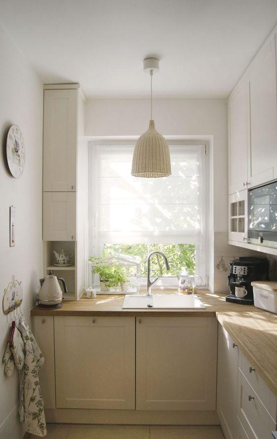 una piccola cucina angolare da fattoria neutra con controsoffitti leggeri in macellaio e lampade intrecciate e luce naturale