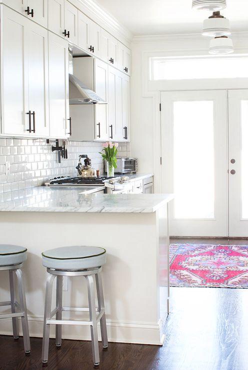 una cucina a L di una fattoria bianca con controsoffitti in pietra bianca e un backsplash in piastrelle bianche della metropolitana più maniglie scure