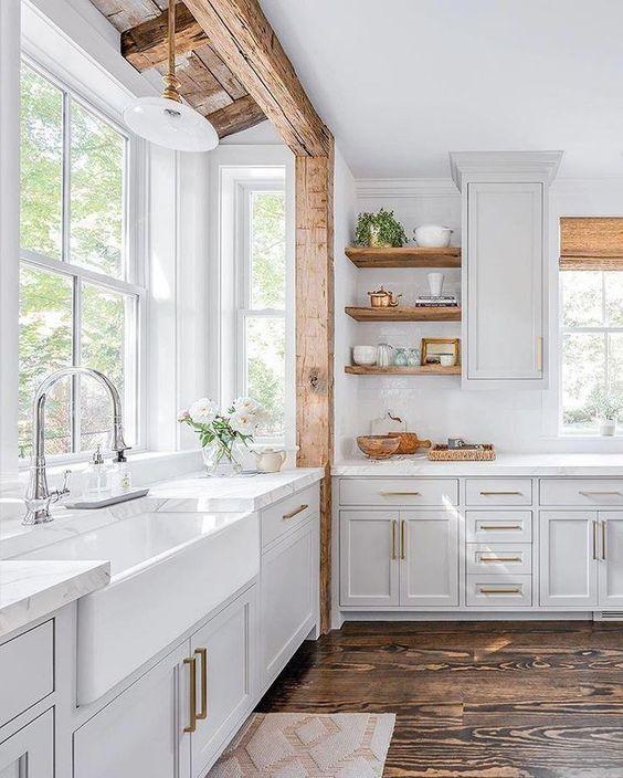 una cucina da fattoria bianca con una trave in legno, ripiani in legno e sfumature intrecciate più tocchi in ottone