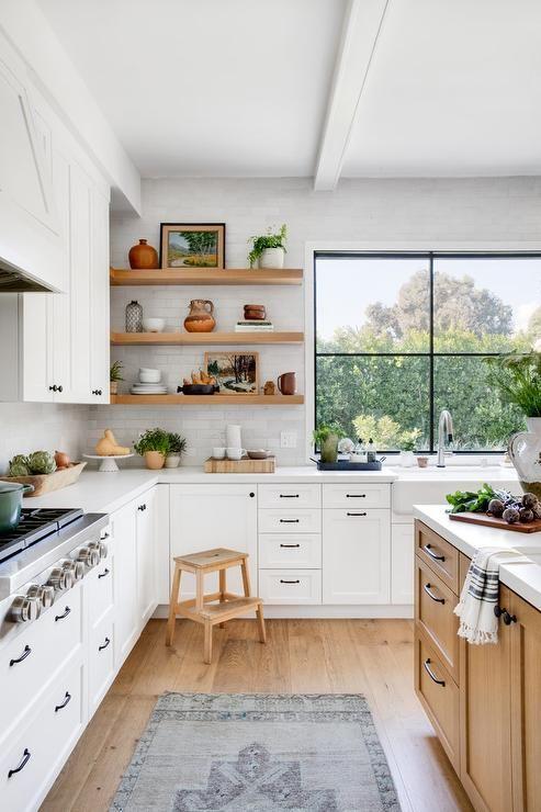 un'accogliente cucina angolare bianca in stile rustico con elementi in legno chiaro e una grande finestra