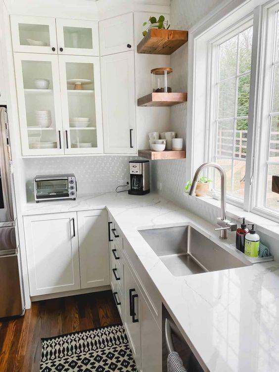 una cucina angolare di una fattoria bianca con ripiani in pietra bianca, mensole in legno riccamente colorate