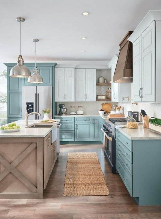 una cucina ad L bicolore turchese e azzurro, con isola cucina in legno e lampade a sospensione