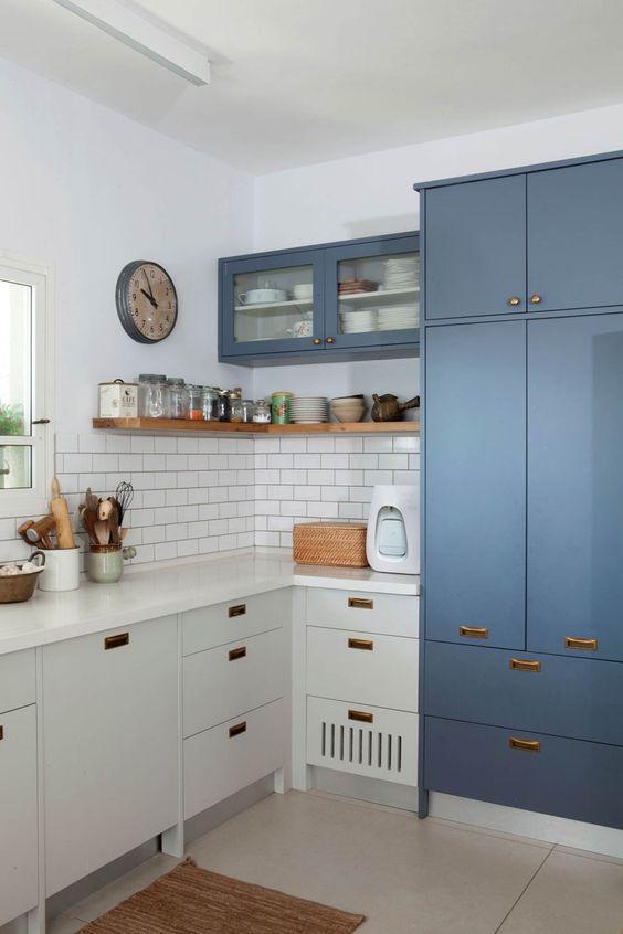 una cucina angolare bicolore con maniglie in rame e un paraschizzi in piastrelle bianche della metropolitana e una finestra
