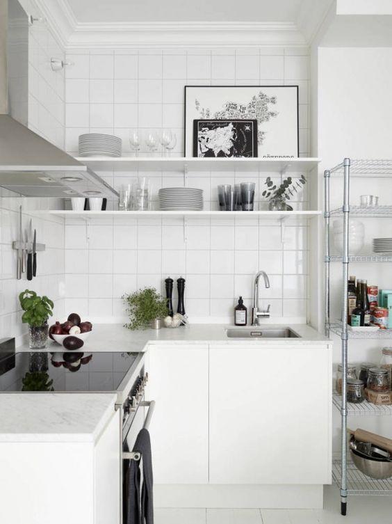 una cucina ad angolo nordica bianca con un paraschizzi in piastrelle bianche, elettrodomestici in acciaio inossidabile è uno spazio molto arioso