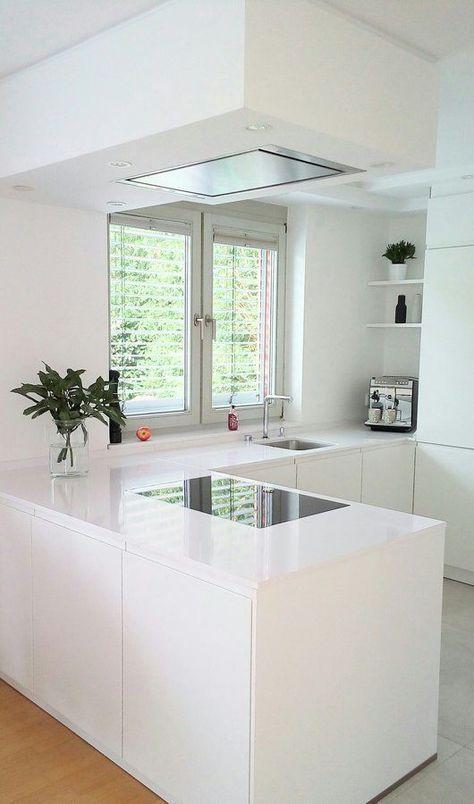 una cucina angolare bianca minimalista a forma di L con cappa coordinata e una finestra e una vista è molto ariosa e accogliente
