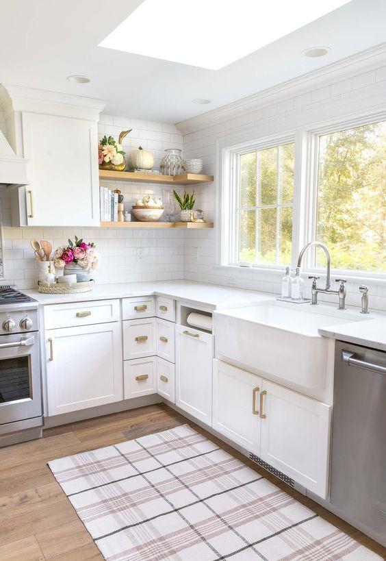 una cucina angolare bianca ad L con maniglie in ottone, ripiani aperti e finestre più un lucernario è uno spazio molto accogliente