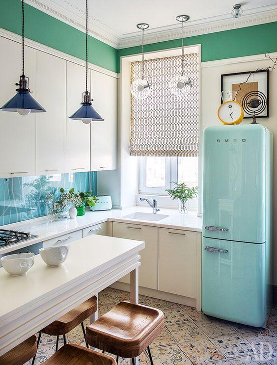 una cucina ad angolo bianca con un frigorifero blu, lampade a sospensione e piastrelle a motivi geometrici sul pavimento è uno spazio carino e accattivante