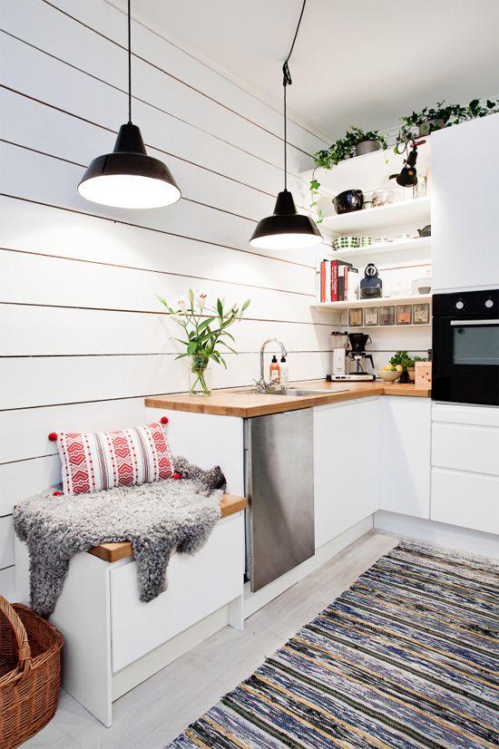 una cucina ad angolo scandinava bianca con controsoffitti butcherblock, lampade a sospensione nere e piante in vaso