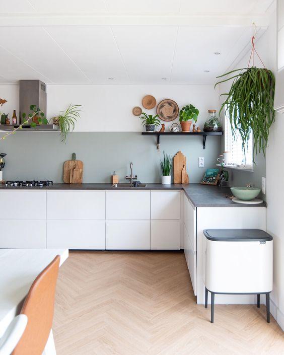una cucina ad angolo boho bianca a forma di L con un paraschizzi grigio, controsoffitti in pietra grigia, vegetazione in vaso è vivace e fresca