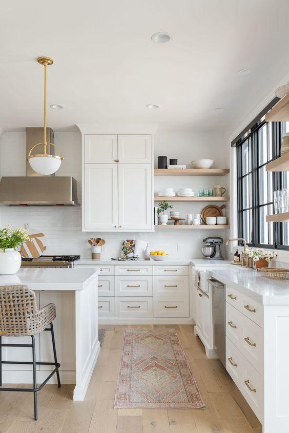 un'elegante cucina ad angolo bianca con isola cucina, scaffali aperti, lampade accattivanti e tocchi di ottone