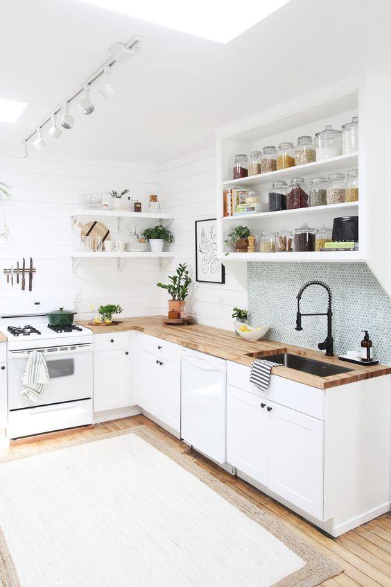 una cucina ad L in bianco, con controsoffitti butcherblock e un lucernario più un paraschizzi in piastrelle blu penny
