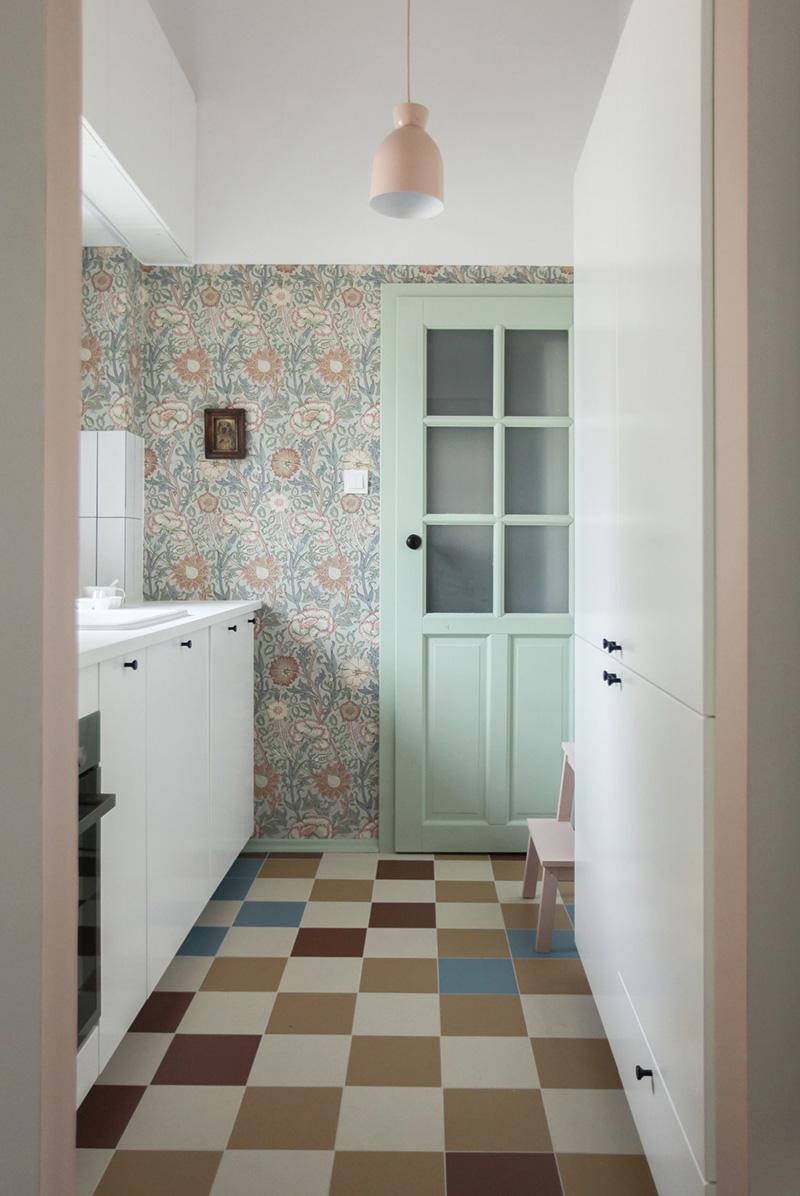 C'è una piccola cucina con carta da parati scandinava e mobili bianchi, piastrelle colorate sul pavimento