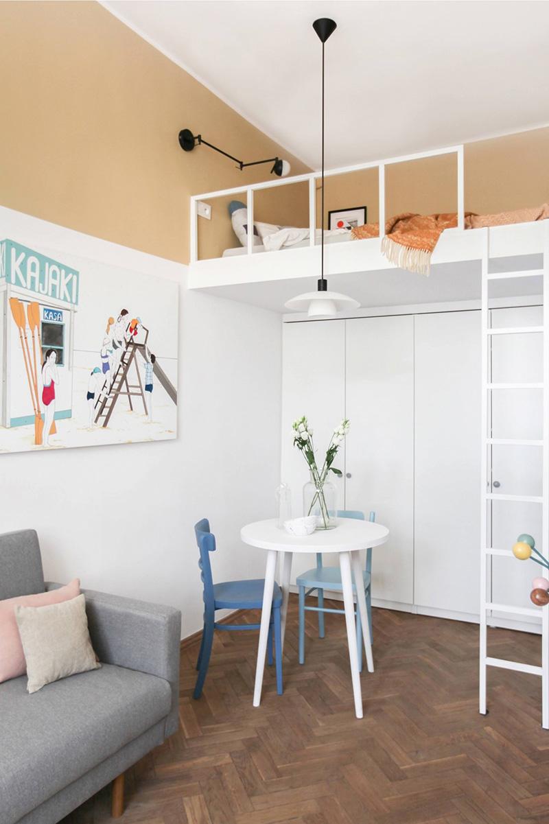 C'è una piccola sala da pranzo, alti armadi e una camera da letto soppalcata con una scala e lampade fantastiche