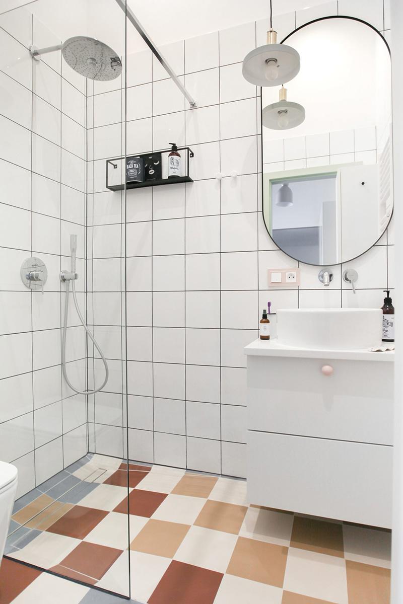 Il bagno è rivestito con piastrelle quadrate bianche e piastrelle colorate sul pavimento, e qui c'è tutto il necessario