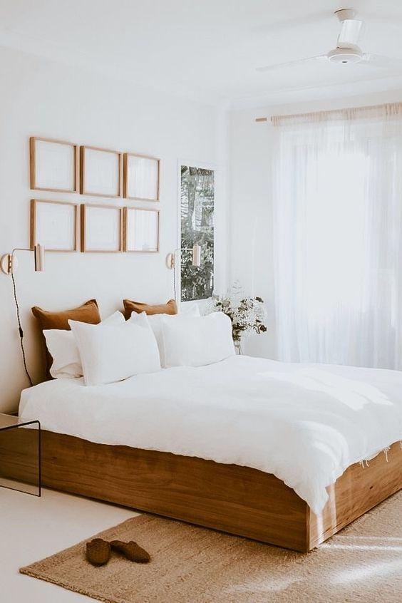 una camera da letto neutra con una galleria a muro, un letto in legno con biancheria da letto neutra, lo spazio sembra più grande grazie ai colori