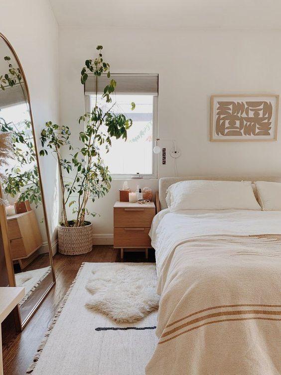 una combinazione di colori neutri e un grande specchio sul pavimento rendono la camera da letto grande e molto accogliente