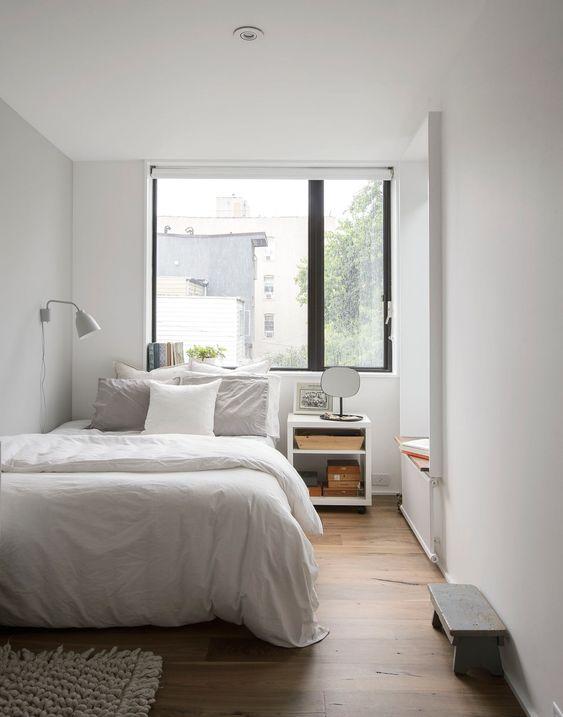 una piccola camera da letto in colori neutri, con una grande finestra sopra il letto è piena di luce naturale e sembra più grande