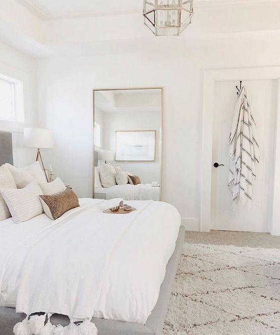 una camera da letto neutra della fattoria sembra più grande grazie alla combinazione di colori neutri e grazie a un grande specchio
