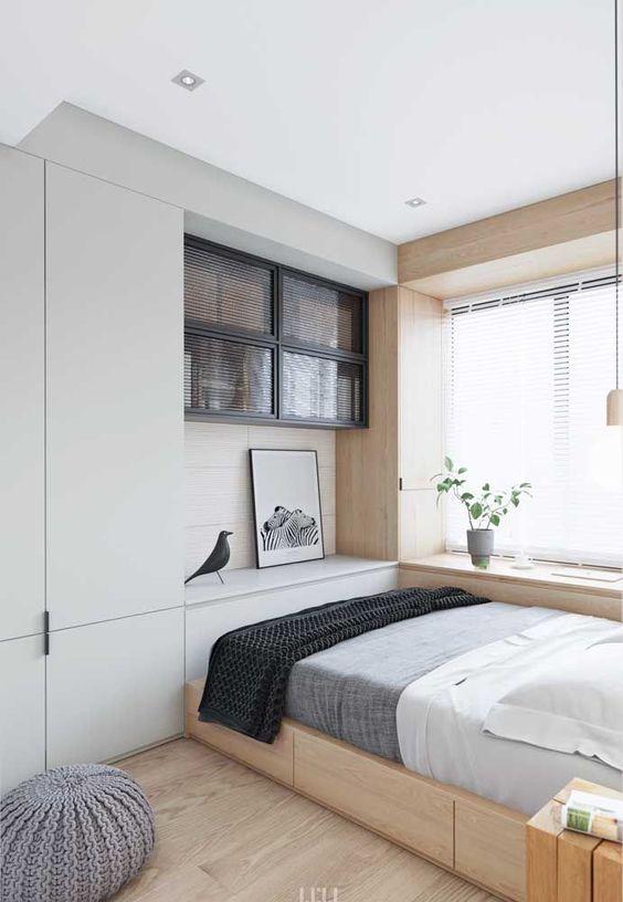 una piccola camera da letto sembra più grande grazie alla combinazione di colori neutri, una grande finestra vicino al letto e mobili dal pavimento al soffitto