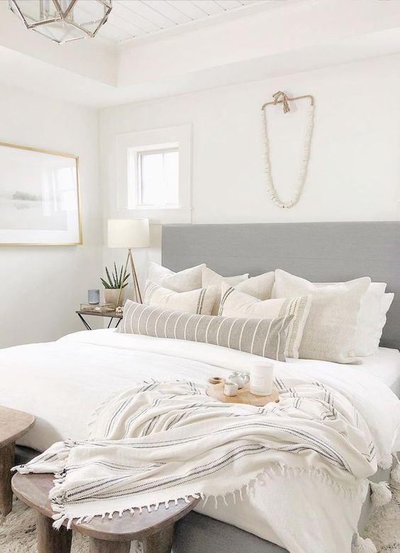 una piccola camera da letto neutra sembra più grande a causa di una testiera estesa, una combinazione di colori neutri e abbastanza luce