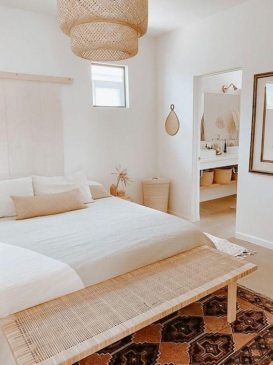una piccola camera da letto sembra più grande grazie allo schema di colori neutri e ai pezzi di vimini e tessuti che vengono aggiunti per l'arredamento