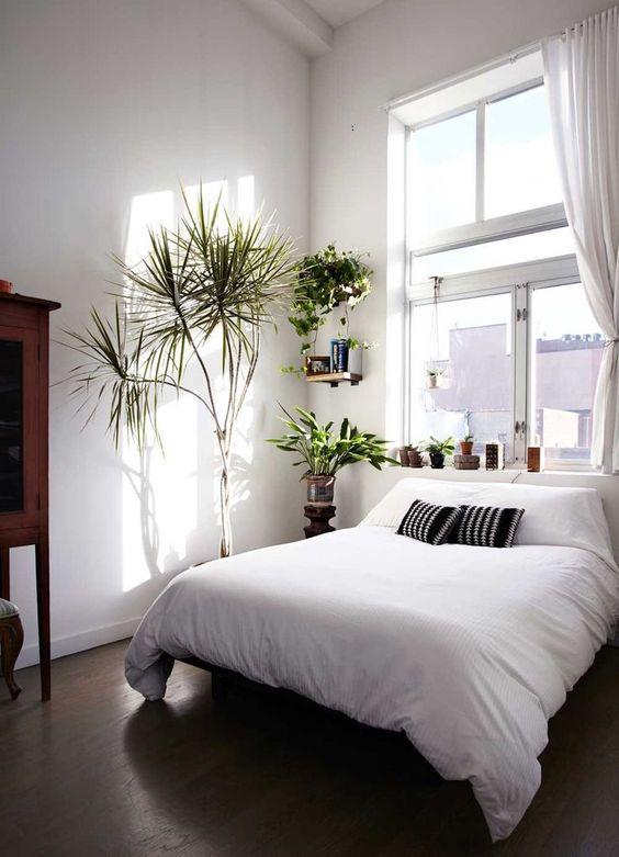 una piccola camera da letto con una finestra sopra il letto che riempie l'intero spazio di luce naturale, anche le pareti bianche aiutano in questo