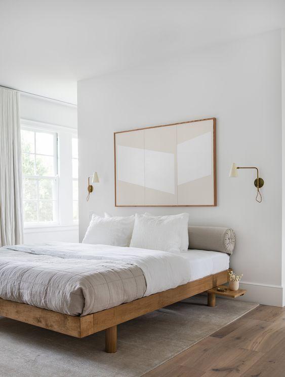 una piccola camera da letto resa visivamente ampliata con uno schema di colori neutri e un'opera d'arte sovradimensionata sopra il letto