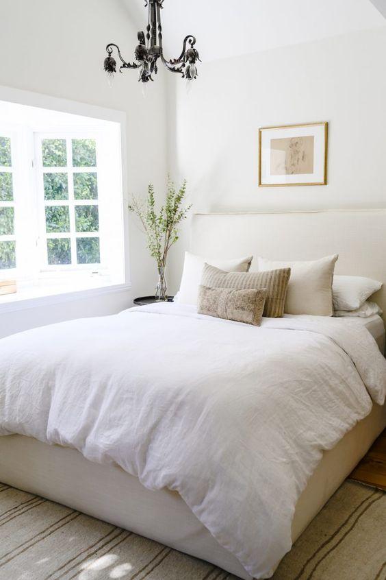 una piccola camera da letto con una combinazione di colori neutri e un bovindo che porta molta luce all'interno sembra più grande