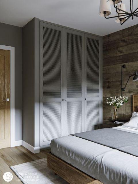 una piccola camera da letto con armadi dal pavimento al soffitto per farla sembrare più grande e dare più spazio di archiviazione