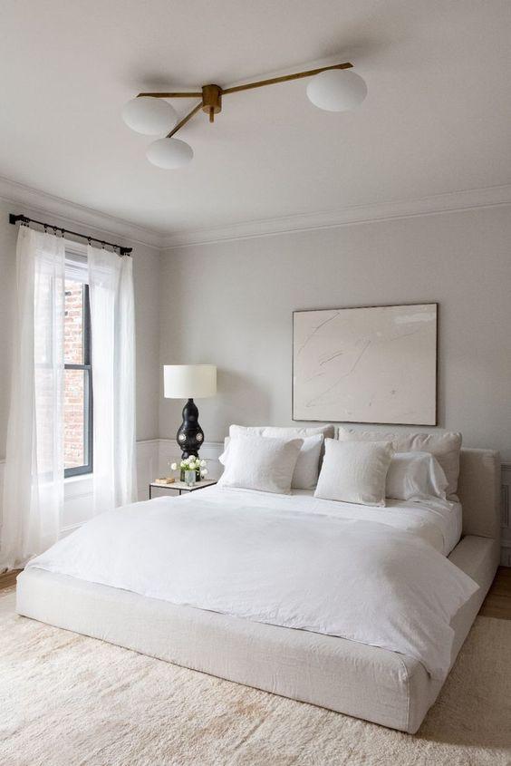 una piccola camera da letto accogliente realizzata in una tavolozza di colori neutri, con biancheria da letto neutra e un lampadario retrò