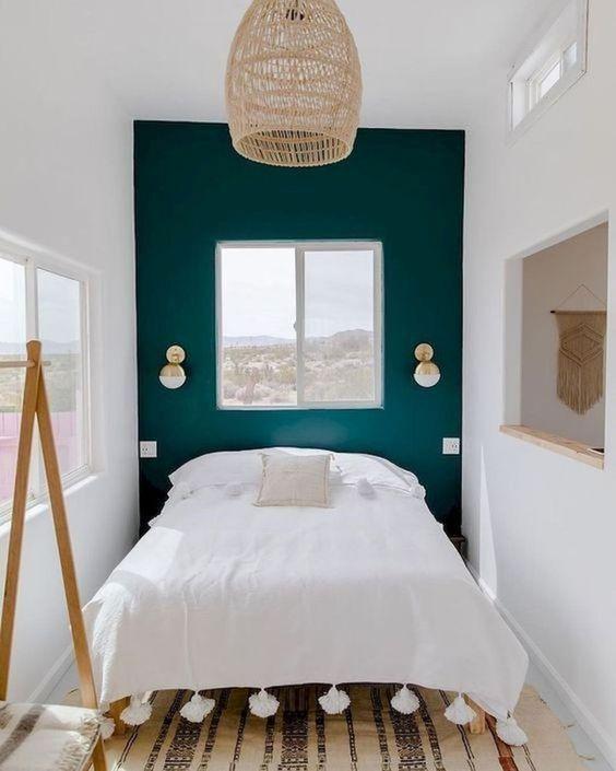 una piccola camera da letto ampliata con uno schema di colori neutri, uno specchio e diverse finestre e si sente accogliente
