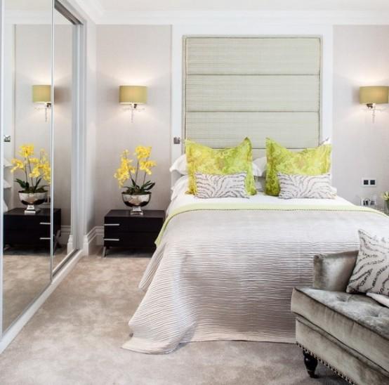 una testiera orizzontale sovradimensionata sopra il letto e le ante scorrevoli in vetro dell'armadio ampliano visivamente lo spazio