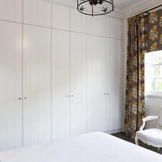 una piccola camera da letto con decorazioni bianche su bianco e un pavimento a contrasto e tende floreali scure per un contrasto audace