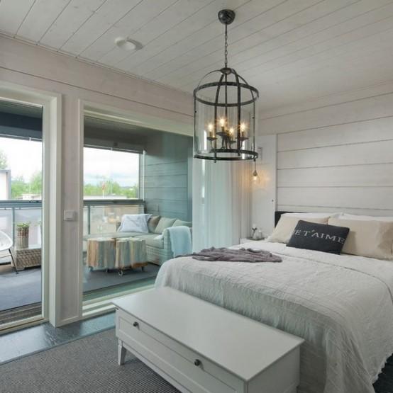una camera da letto neutra della fattoria con beadboard orizzontali che coprono le pareti e il soffitto per espandere visivamente la camera da letto