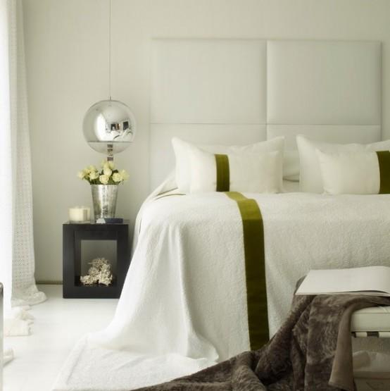 una testiera oversize con pannelli imbottiti orizzontali e lampade a sospensione a specchio utilizzate per ampliare lo spazio