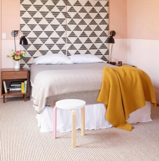 una camera da letto pastello morbida sembra più luminosa grazie ai pannelli geometrici estesi sopra il letto