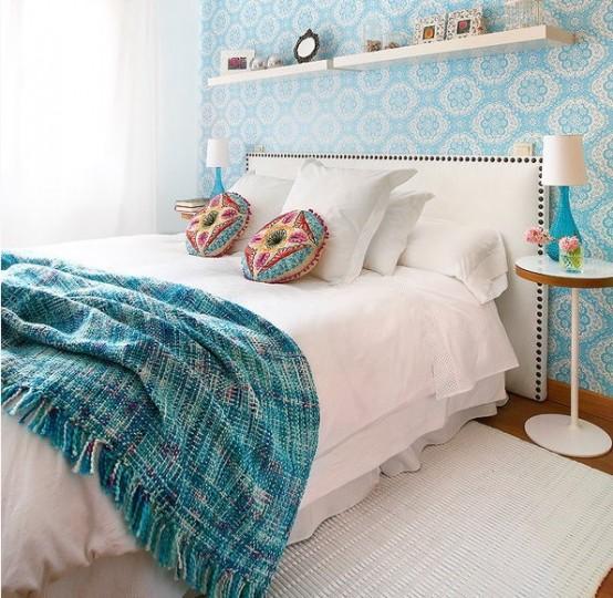 un duo di mensole orizzontali sopra il letto e molti neutri fanno sembrare la camera da letto più grande e accogliente