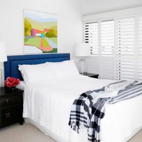 una camera da letto neutra con un tocco di colore: una testiera blu scuro, un comodino nero, un'opera d'arte colorata, sembra più grande e più audace