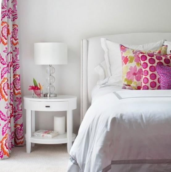 una piccola camera da letto decorata solo in bianco e con solo un tocco di colori vivaci - cuscini e tende - sembra audace e fresca