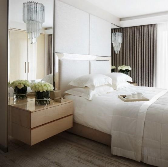 una testiera sovradimensionata più pannelli imbottiti su di essa e specchi su entrambi i lati del letto rendono la camera da letto più ampia e fresca