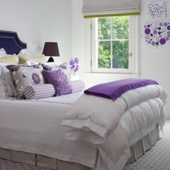 il colore bianco come quello principale per l'arredamento della camera da letto rende lo spazio più grande e accogliente, e il viola audace aggiunge un tocco di contrasto allo spazio