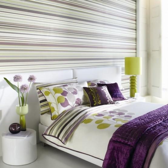 un muro di accento con strisce orizzontali rende la camera da letto più ampia e più grande allo stesso tempo