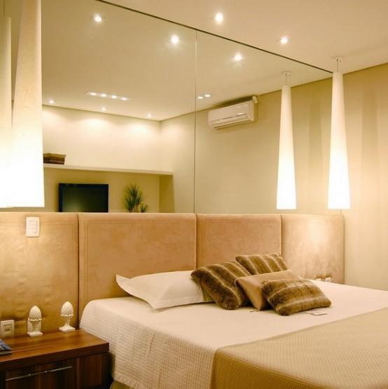una camera da letto neutra e pastello con specchi a parete e testiera imbottita sembra più grande e più fresca e le luci integrate si aggiungono allo spazio