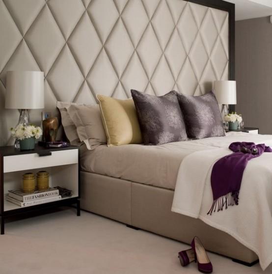 una camera da letto neutra con una testiera imbottita estesa di grandi dimensioni sembra lussuosa e molto grande