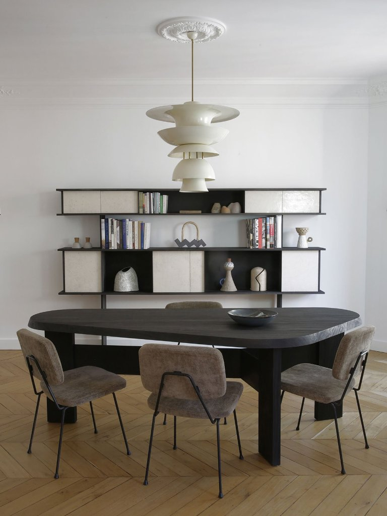 La sala da pranzo mette in mostra un tavolo in legno scuro, alcune sedie fresche e un raffinato pezzo di stoccaggio al muro