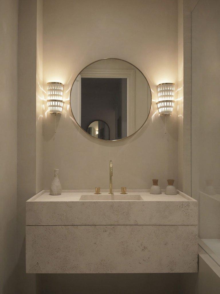 Il bagno è neutro, con un lavabo in marmo, finiture dorate e applique chic