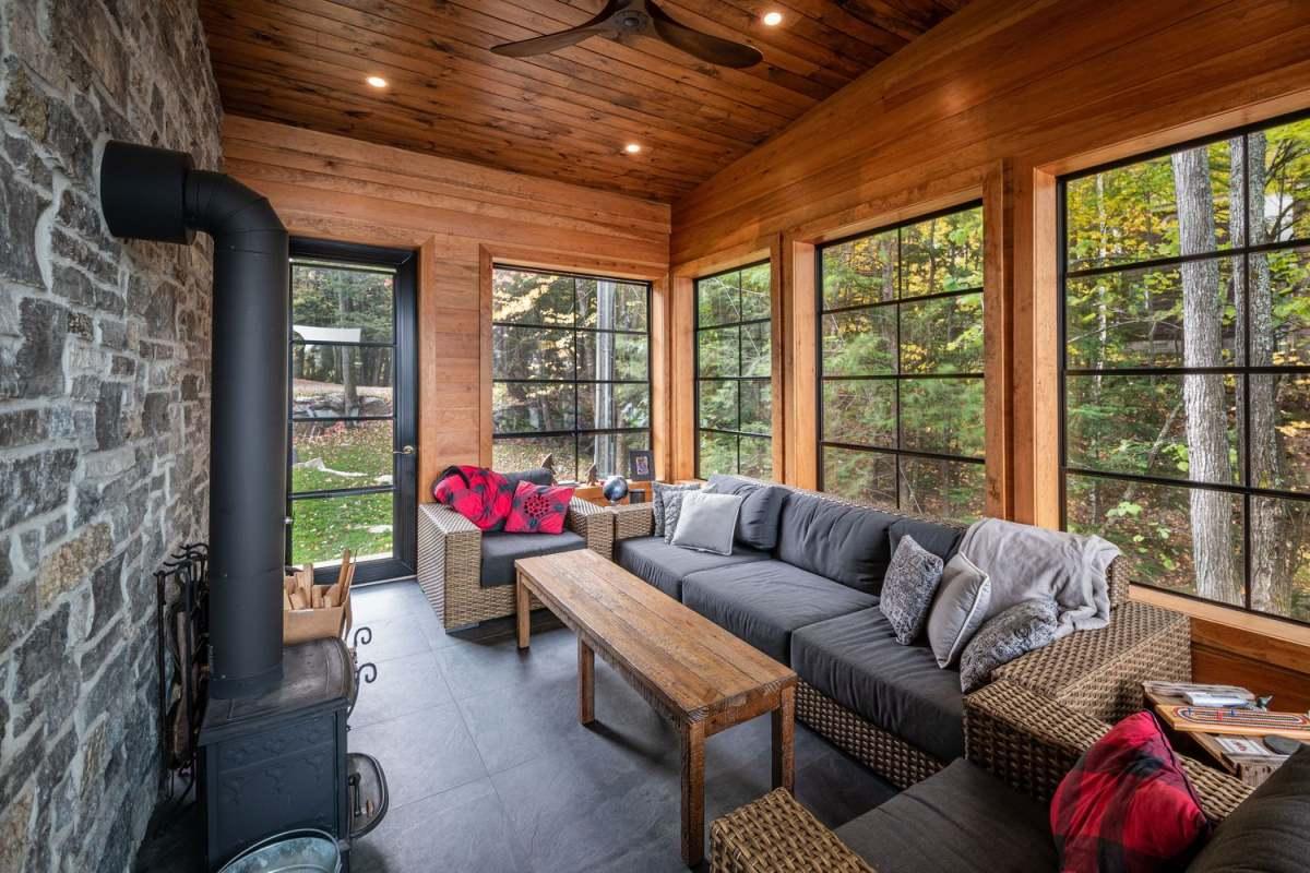 C'è una veranda coperta con mobili intrecciati, tessuti eleganti e un focolare più luci