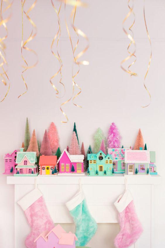 una mensola natalizia luminosa e divertente con calze rosa e verdi, casette rosa e verdi e piccoli alberi di orpello per un tocco divertente